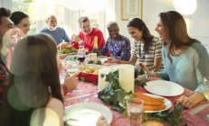 Laughing multi-ethnic family enjoying Christmas dinner at table — Stock Photo