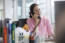 Smiling businesswoman talking on telephone working at computer in office — Stock Photo