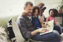 Smiling multi-ethnic father reading book with daughter on sofa — Stock Photo