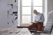 Бізнесмен, використовуючи цифровий планшетний в офісі вікно — стокове фото