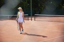Молодий тенісистка прогулянки з ракетки теніс на корті Сонячний глини — стокове фото