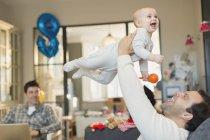 Мужчины гей родителей подъема и играть с маленьким сыном в гостиной — стоковое фото