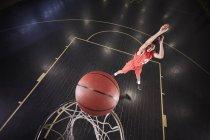 Молодой баскетболист бросает мяч на корте в спортзале — стоковое фото