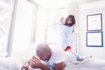 Playful couple pillow fighting in bedroom — Stock Photo