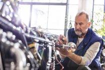 Старші чоловіки мотоцикл механік фіксації мотоцикл в майстерні — стокове фото