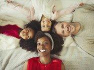Obenliegende Porträt Lächeln multi-ethnischen junge Familie auf Bett — Stockfoto