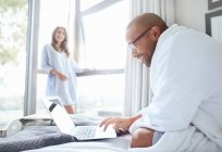 Smiling woman watching boyfriend in bathrobe reading laptop on bed — Stock Photo