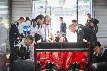 Команда пит-стопа готовит гоночный автомобиль в ремонтном гараже — стоковое фото