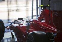 Red formula one race car in repair garage — Stock Photo