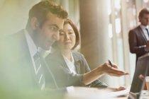 Gli uomini d'affari che lavorano al computer portatile in riunione — Foto stock