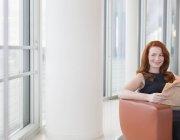 Lächelnd geschäftsfrau mit roten Haaren Zeitunglesen im Büro lounge — Stockfoto