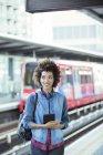 Жінка тримає цифровий планшетний в залізничного вокзалу — стокове фото