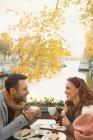 Junges paar Kaffee zu trinken und Essen Käsekuchen Dessert in Herbst Straßencafé Kanal entlang — Stockfoto