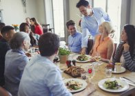 Waiter serving food to friends dining at restaurant table — Stock Photo