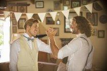 Bräutigam und Trauzeuge halten Händchen im häuslichen Zimmer — Stockfoto
