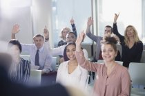 Smiling business people asking a question in conference audience — Stock Photo
