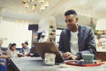 Homme d'affaires créatif travaillant à un ordinateur portable dans un café — Photo de stock