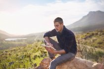 Young man using digital tablet on rock in sunny, remote valley — Stock Photo