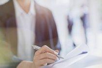 Fermer femme d'affaires prenant des notes en réunion — Photo de stock
