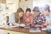 Grupo de adolescentes que utilizan juntos tableta digital en la mesa en la cocina - foto de stock