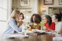 Lächelnde Frauen Kaffee trinken und Reden am Tisch im restaurant — Stockfoto