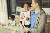Portrait smiling multi-ethnic father and daughter in kitchen — Stock Photo