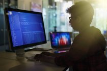 Boy student programming at computer in dark classroom — Stock Photo