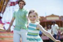 Menina puxando seu pai no parque de diversões — Fotografia de Stock