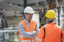Smiling foreman talking to construction worker at construction site — Stock Photo