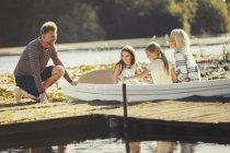 Famille en canot au quai ensoleillé du lac — Photo de stock