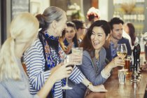 Smiling women friends drinking wine at bar — Stock Photo