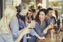 Lächelnde Frauen Freunde trinken Wein in Bar — Stockfoto