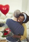 Wife receiving Valentines Day rose bouquet and balloon, hugging husband — Stock Photo