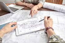 Architects reviewing and discussing complex digital blueprint in meeting — Stock Photo