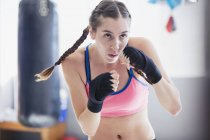 Determined, tough young female boxer shadowboxing in gym — Stock Photo