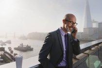 Бизнесмен разговаривает по мобильному телефону на солнечном городском мосту, Лондон, Великобритания — стоковое фото