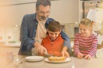 Padre che taglia e serve torta ai bambini in cucina — Foto stock