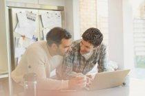 Pareja gay masculino usando laptop y tomando café en la cocina - foto de stock