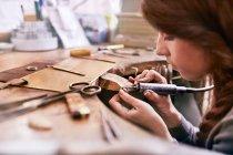Sérieux bijoutier femelle ciblé à l'aide de matériel en atelier — Photo de stock