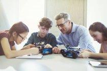 Male teacher helping students assembling robotics in classroom — Stock Photo