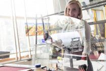 Portrait smiling stained glass artist lifting glass in studio — Stock Photo