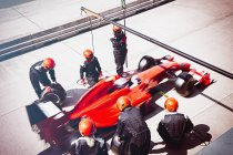 Pit crew replacing tires on formula one race car in pit lane — Stock Photo