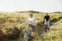 Playful mature couple riding bicycles on sunny beach grass path — Stock Photo