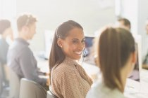Smiling female telemarketers wearing headsets talking in sunny office — Stock Photo
