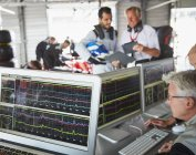 Formula one racing team reviewing diagnostics on computers in repair garage — Stock Photo