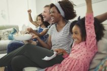 Enthusiastic multi-ethnic young family cheering, watching sports on sofa — Stock Photo