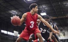 Молодой баскетболист капает мяч, играет в гимнастический зал — стоковое фото