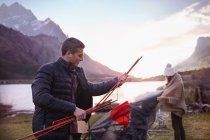 Giovane coppia piantare la tenda al campeggio sul lago di montagna — Foto stock