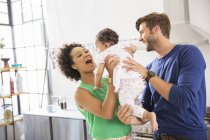Happy parents holding their baby daughter in domestic kitchen — Stock Photo