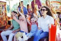 Família no carrossel no parque de diversões — Fotografia de Stock